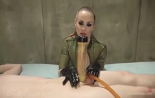 Dominatrix in latex vacuuming her slave's cock