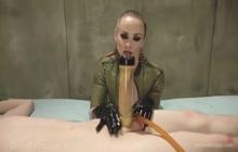 Dominatrix in latex vacuuming her slave's cock